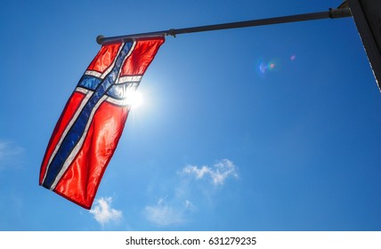 Norwegian flag up close, towards the sun on beautiful blue sky