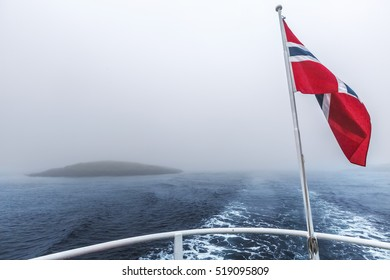 Norwegian flag flying in the wind over the sea on heavy foggy day in Northern Norway