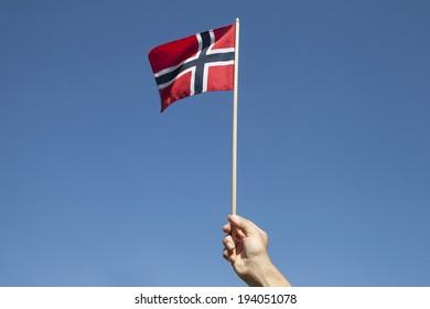 Norwegian flag in hand against blue sky.
