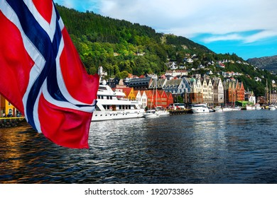 Norwegian flag with the port of Bergen and view on the historical buildings of Bryggen in Bergen, Norway