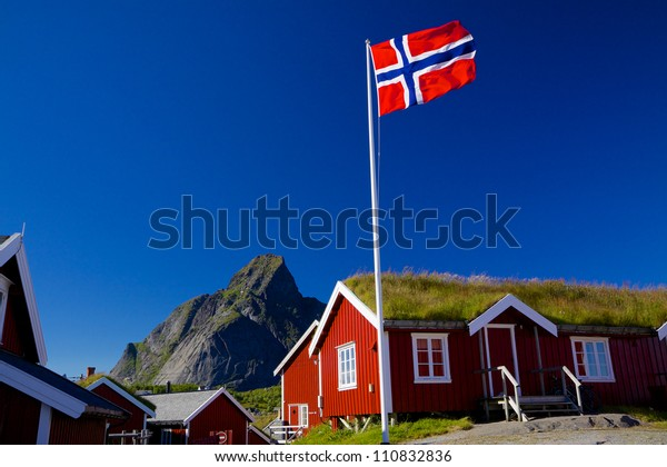 Norwegian flag with typical norwegian red wooden house with sod roof on Lofoten islands