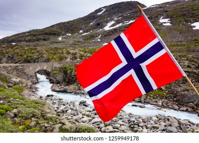 Norwegian flag waving against mountains landscape. Travel, holidays and adventure concept.