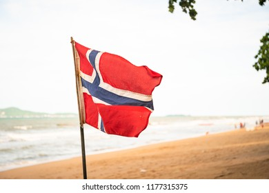 The Norwegian flag waving in the wind an amazing sandy beach