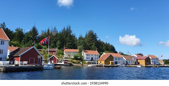 Norwegian flags waving in the wind on 17 may constitution day view from a boat in the archipelago of southern Norway with an idyllic small town in the background, in Åvik Norway - May 17, 2020