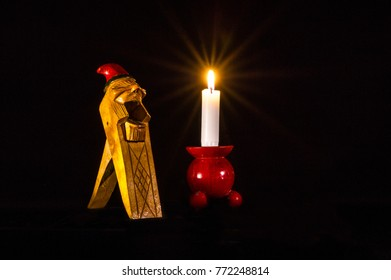 A Norwegian Gnome Handcarved Wooden Nut Cracker together with a candlelight on a typical red wooden candlestick.