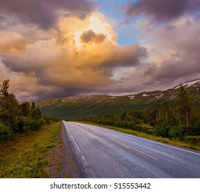 Norwegian highway road in the mountains and dramatic sunset sky with  fluffy clouds in Norway, Europe