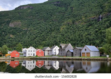 Norwegian houses reflecting in the water on the shore of Sognefjord at Laerdal, Norway.