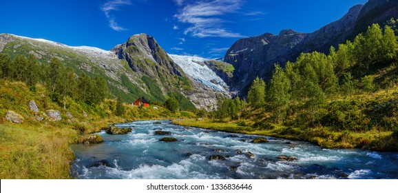 Norwegian landscape with milky blue glacier river, glacier and green mountains. Briksdal or Briksdalsbreen glacier in Olden, Norway. Panorama