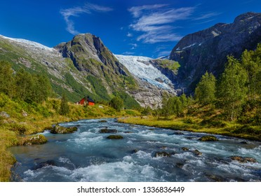Norwegian landscape with milky blue glacier river, glacier and green mountains. Briksdal or Briksdalsbreen glacier in Olden, Norway