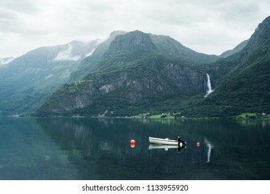 Norwegian landscape with mountain and Feigumfossen waterfall. White boat in the Lusterfjord fjord. Summer day. Commune Luster, Norway