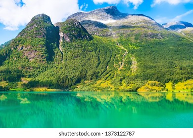 Norwegian landscape with Nordfjord fjord, green mountains, snow in Olden, Norway