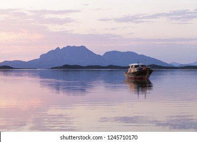 Norwegian landscape with old wooden boat, reflection on still sea surface, mountain Donna on background. Photographed in Helgeland, Norway.