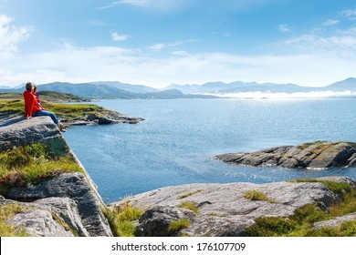 Norwegian landscape: two women enjoying view at Kvernesfjorden with clouds floating over water