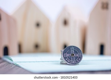 Norwegian Norge coin on bank book with blurred lines of wooden toy house background for Norway property business concept