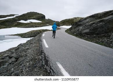 Norwegian Scenic Route Aurlandsfjellet. A guy in a blue jacket walks the mountain road Bjorgavegen in Norway