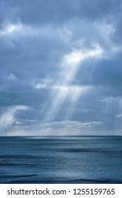 Norwegian sea in winter with sun rays through clouds. Lofoten islands, Norway