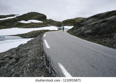Norwegian view with guy in a blue jacket in the mountains. Landscape near the snowy road bjorgavegen, Norway. Tourist Route Aurlandsfjellet runs from Aurlandsvangen to Laerdalsoyri