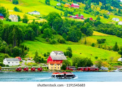 Norwegian village landscape with fjord, mountains and colorful houses, boat in Olden, Norway