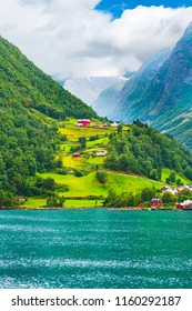 Norwegian village landscape with turquoise fjord water, mountains and colorful houses, Norway, Flam