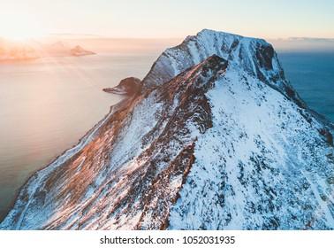 Norwegian winter sunny mountain landscape blue sky view with mountains, fjord, Norway, Ryten peak - famous mountain in Lofoten Islands, Moskenes municipality, Nordland, shot from drone