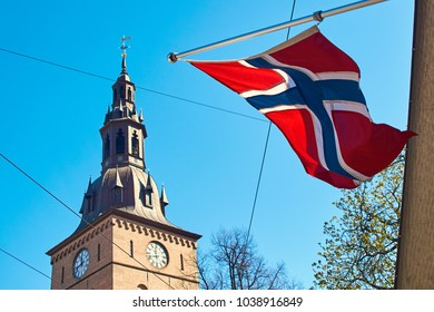 Norwegin flag waving on a sunny spring day with Oslo Cathedral on background