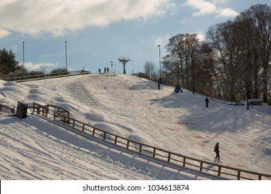 Norwich, Norfolk, England, UK - February 27 2018 : Man skiing at Norfolk Snowsports Club on Whitlingham Lane, Trowse Newton, on the dry ski slope covered in snow