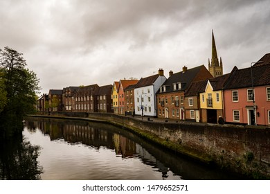 Norwich, Norfolk, UK – April 28 2019. Standing on Fye Bridge in Norwich looking down the River Wensum, the traditional houses along the historic Quayside and the cathedral on the skyline.