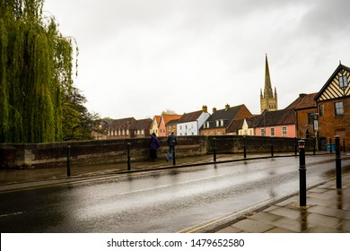 Norwich, Norfolk, UK – April 28 2019. A couple stop on Fye Bridge in Magdalen Street, Norwich and look at the view down the River Wensum, the historic Quayside and the cathedral on the skyline.