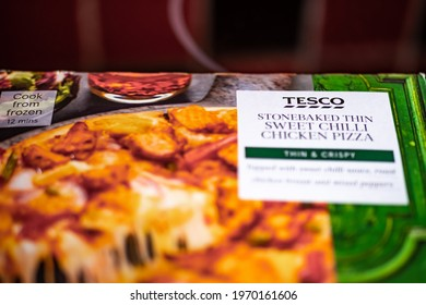 Norwich, Norfolk, UK - April 30 2021. Close and selective focus of a Tesco branded readymade frozen stone baked thin sweet chilli chicken pizza in its packaging ready for Saturday night dinner