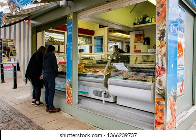 Norwich, Norfolk, UK – April 6 2019: Young couple choosing fresh fish from a mobile stall selling seafood on Norwich market