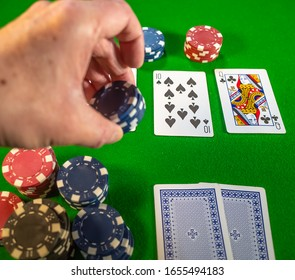Norwich, Norfolk, UK – February 22 2020. Poker player placing the chips during a round of betting in a game of Texas Holdem poker, with the cards in sharp focus and the player's hand intentionally sof