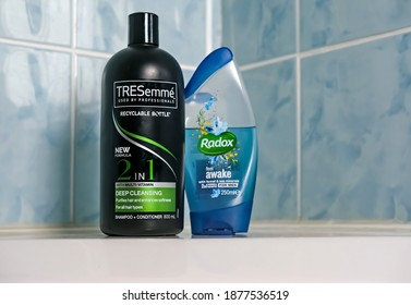 Norwich, Norfolk, UK - November 29 2020. An illustrative editorial photo of a bottle of TRESemme 2 in 1 hair shampoo and conditioner and a bottle of Radox shower gel on the side of a white bath