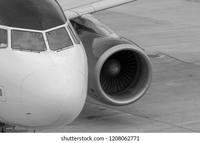 The nose of an aircraft with cockpit and engine at the wing as black and white