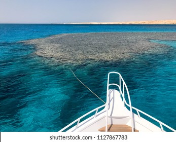 The nose, the front of the white yacht, the boat, the ship standing on the jig, parking, anchoring in the sea, the ocean with blue water with coral reefs against the backdrop of the mountains.