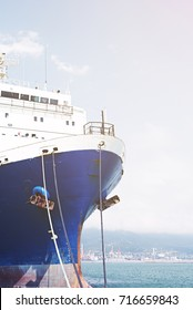 Nose large cargo ship moored on the background of blue sky. Ship rope. Bright sun above the deck.