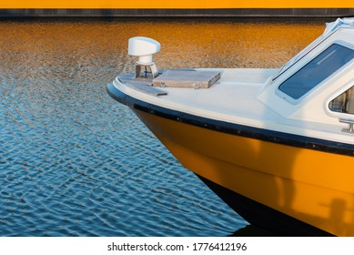 Nose of a yellow and white fiberglass speedboat moored at a marina