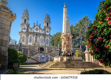 Nossa Senhora dos Remédios Sanctuary in Lamego, Portugal, with the church in the background and fountain with obelisk in the foreground, on a blue sky day.