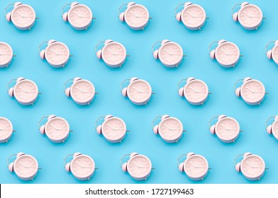 Nostalgia repetitive wallpaper and passing of time concert with minimalist seamless pattern layout of pastel pink mechanical alarm clock isolated on vibrant blue background