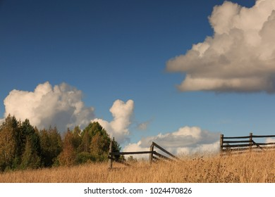 Nostalgic autumn landscape with old wooden gate and railing in the field with trees in the distance and beautiful blue sky with white clouds