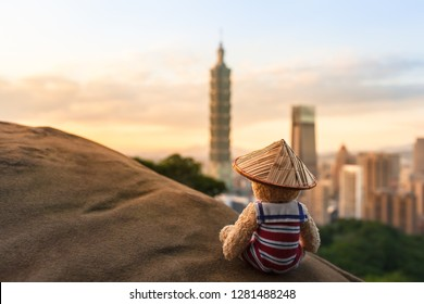 Nostalgic dressed teddy bear wear sailor suit and chinese straw hat, sitting at rock high above modern Taipei city (Taiwan), view to sky and buildings (large copy space)