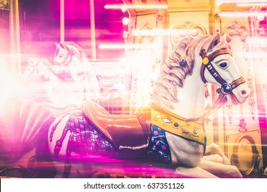 Nostalgic Horse Detail of Carousel Spinning with Pink Light Blurs at Night