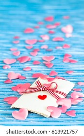 Nostalgic love letter with ribbon and many pink hearts around up to the blue background (copy space)/Love Gift on Blue