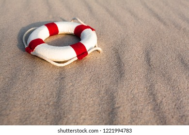 Nostalgic miniature white life buoy with rope and red stripes at wavy beach sand background (copy space)