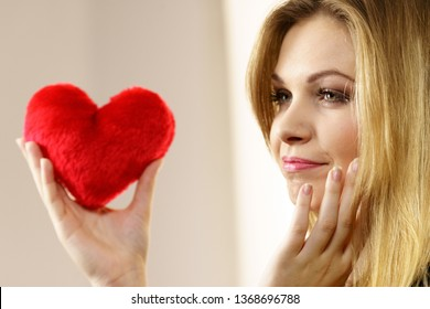 Nostalgic pretty female holding and looking at red heart shaped small pillow, thinking of falling in love.