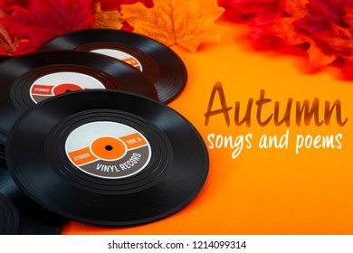 Nostalgic songs, fall music and melancholy concept with vintage vinyl records surrounded by autumn red and yellow leaves on orange background with the text autumn songs and poems