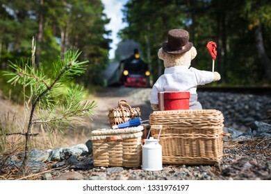 Nostalgic teddy bear with big luggage waiting at railway track for approaching steam train, waving red signal flag