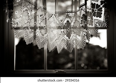 Nostalgic view through old fashioned window with lace curtain