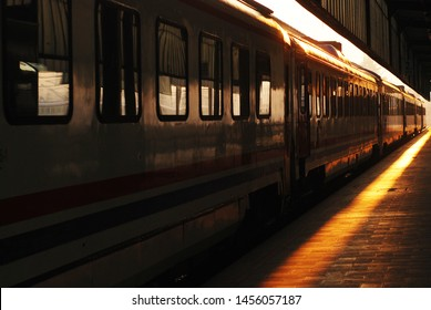 Nostalgic view of a train station at sunset. Railway and railroad with pastel colours. Redish tones. Beautiful moment of a travel. Beginning of a journey, travel. Locomotive view at station.