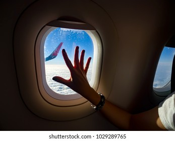 Nostalgic woman passenger hand touching plane window with view of wing and sky