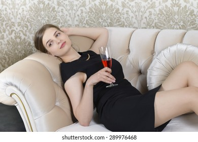Nostalgic Woman Relaxing on Sofa Holding a Glass of Wine
